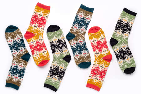 A cute gift or decoration for the celebration of Christmas  New Year. Multicolored knitted socks with an ornament. 版權商用圖片 - 158365929