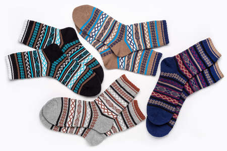 A set of multi-colored knitted socks with an ornament. The concept of cozy home atmosphere in winter. Socks background.