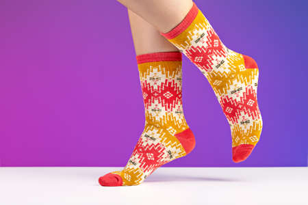 Close-up of colorful soft socks on female legs. Space for design on a blue background. 版權商用圖片
