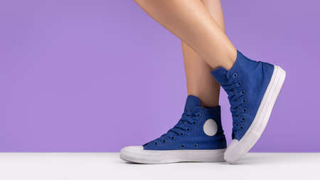 Blue sneakers with laces on female legs. Shoes for sports and travel.