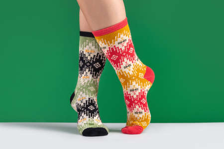 Woman's legs in multicolored knitted socks with ornament, green background. The concept of cozy home atmosphere in winter. 版權商用圖片 - 158365750