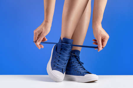 A woman in blue sneakers is tying her shoelaces. Shoes for sports and travel. 版權商用圖片 - 158366819