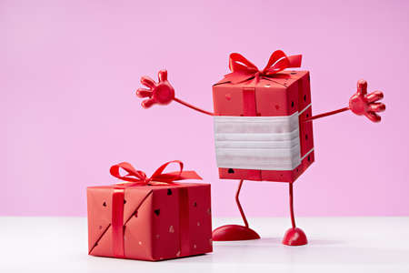 Gift in red box in protective mask. We defeat the virus. Box on legs, with handles. Copy space.