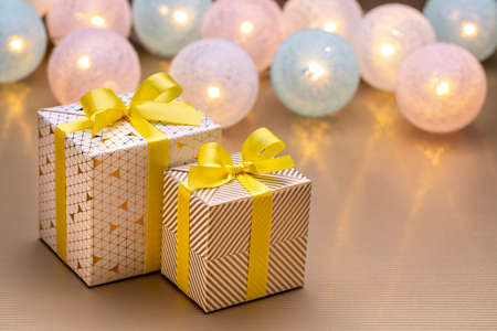 Christmas and New Year's gifts wrapped in shiny paper, with  lanterns in the background. Happy winter holidays concept. 版權商用圖片
