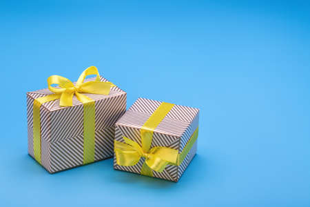 Gift in two boxes, wrapped in holiday paper and tied with yellow ribbon with bow. A surprise for any holiday and event.