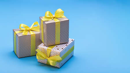 Souvenirs and gifts in elegant packaging for different holidays. Copy space, blue background. 版權商用圖片