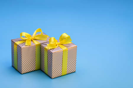 Gift in two boxes, wrapped in holiday paper and tied with yellow ribbon with bow. Surprise for any holiday and event, on wooden background. 版權商用圖片