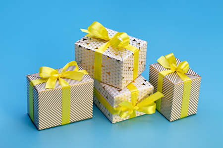 A set of gift boxes in an elegant package with ribbons and bows. Blue background, copy space. 版權商用圖片