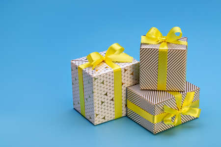 Happy Holidays. Gift boxes with patterns, yellow ribbon with bow on blue background. New Year and Christmas mood.