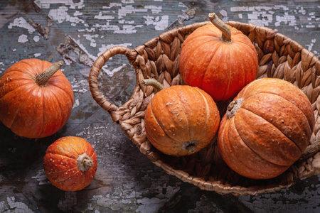 Orange mini pumpkins in a wicker basket on an old gray parcel. Copy space. Happy Halloween.