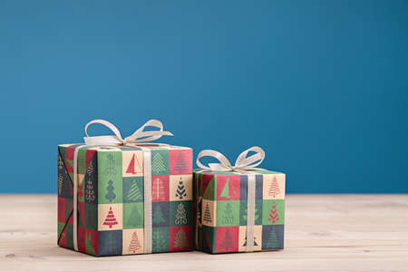 Gifts in boxes, wrapped in paper with Christmas and New Years drawings on light table. Copy space, blue background