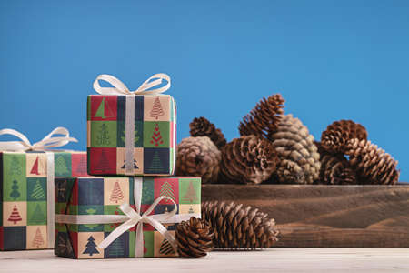 Gifts in boxes, wrapped in paper with Christmas and New Years drawings, a set of pine cones on a light table. Copy space, blue background