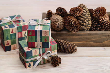 Merry Christmas and Happy New Year. Bright boxes with ribbons and pine cones on light wooden background.