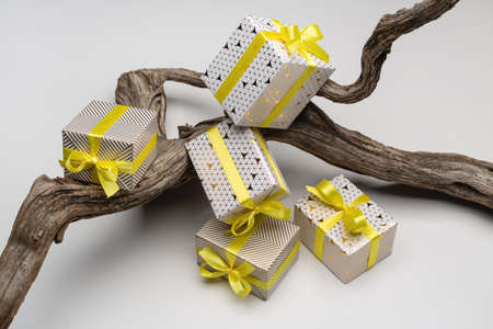 A set of gifts in holiday boxes on snag. Art object on light background, close-up. 版權商用圖片