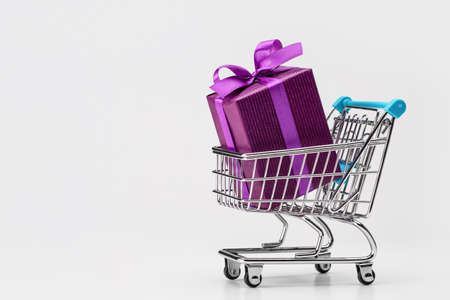 Shopping cart (toy) with gifts in large box, packed in purple paper. Copy space. Discounts, sale.