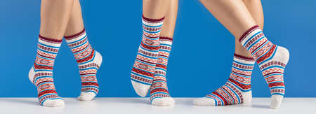 Warm cotton socks for sports and leisure on women's legs. Close-up, blue background.