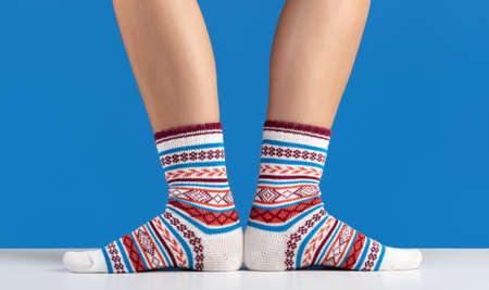 Warm cozy socks on women's legs, blue background. Studio shot, copy space.