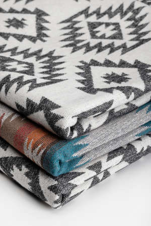 Heap of luxurious, multicolored throw wool blanket, closeup, white background.