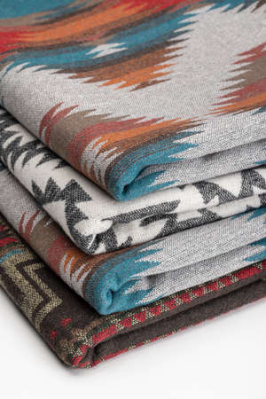 Stacks of Pendleton-style woolen bedspreads in different colors are neatly folded. Gift accessory, studio shot.