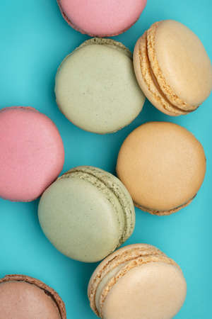 Macaroons, different colors on dark blue background. Top view, close-up.