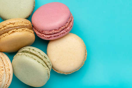 French biscuit biscuits in different colors. Macarons, closeup, studio shot, dark blue background.