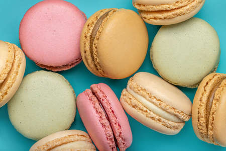 Background from multi-colored macaroons on a bright blue background, top view. Standard-Bild