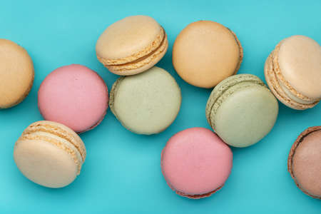Round multicolored macaroons on a bright blue background. Background and wallpaper, close-up.