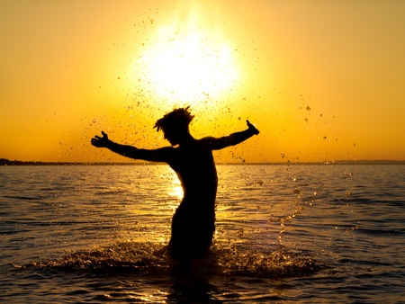 gymnastics silhouette: Swimmer jumping out of sea water on golden sunset