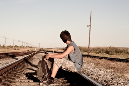 abandonment: Teen boy with problems sitting on railroad Stock Photo