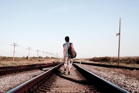 ni�o con mochila: Ni�o adolescente con problema caminando en ferrocarril Foto de archivo