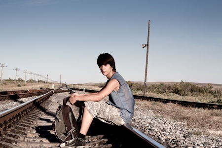 Teen boy with problems sitting on railroad photo