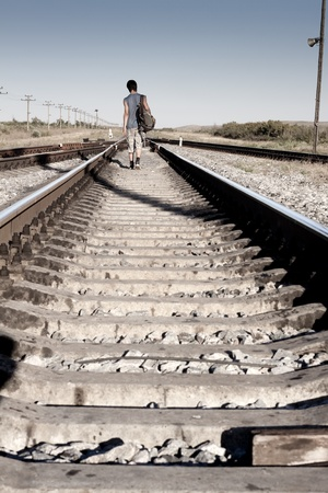 Teen boy with problem walking on railroad photo
