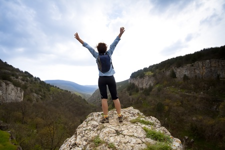 woman on top of the mountain reaches for the sun