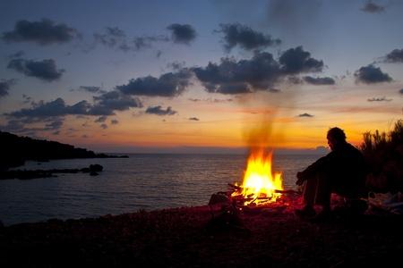 campamento de verano: el hombre sentado junto al fuego Foto de archivo