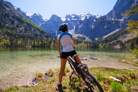 cycleway: Yaung woman riding bike beside a lake in  Alps,  Salzkammergut Austria