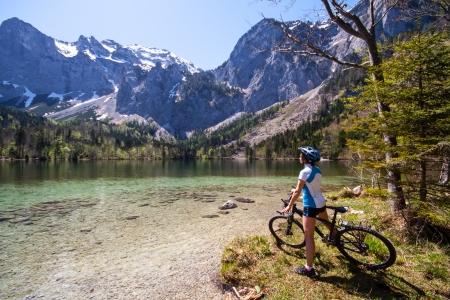 riding bike: Yaung bici donna a cavallo accanto a un lago alpino, Salzkammergut Austria Archivio Fotografico