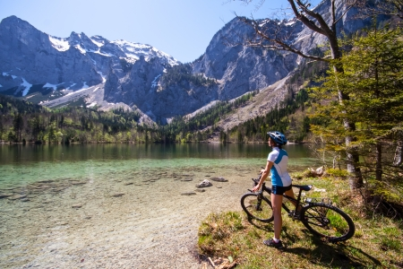 14031429: Yaung woman riding bike beside a lake in  Alps,  Salzkammergut Austria