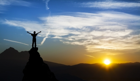 crack climb: man on the top of a rock  meeting sun