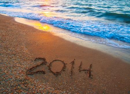 new year 2014 digits on ocean beach sand