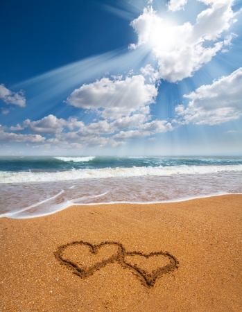 evoking: couple of hearts drawn on the sand of a beach