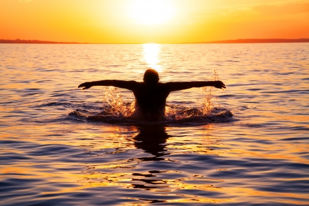 strong young man swiming in the sea over yellow sunrise
