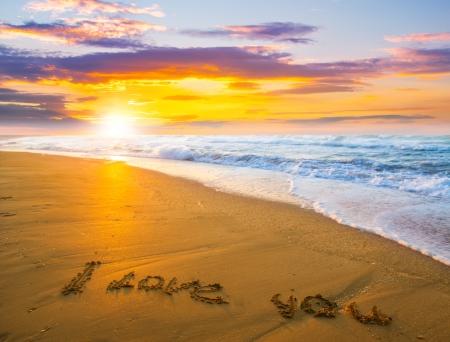 I love you drawn on sand beach  over sunset Foto de archivo