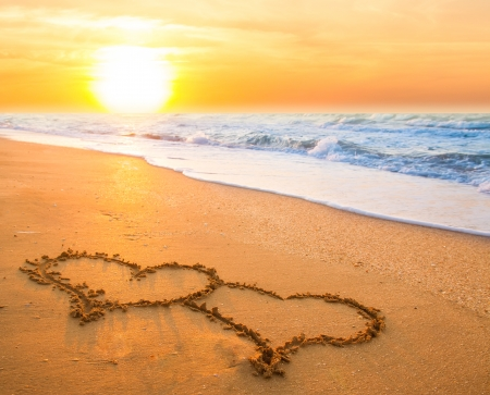 two hand drawn hearts on beach sand over sunset Foto de archivo