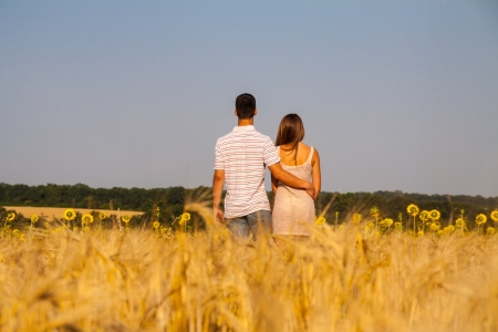 Happy young couple walking together  through wheat field photo