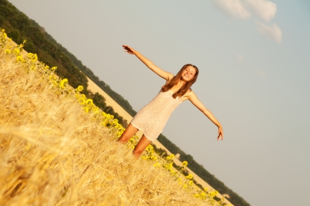 Young beautiful woman jumping and dancing in yellow field, summer outdoor