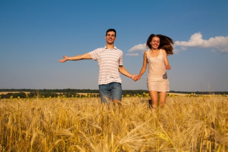 Happy young couple running together  through wheat field Stock Photo