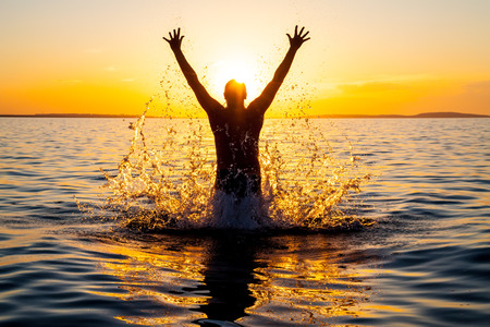 Swimmer jumping out of sea water at warm sunrise