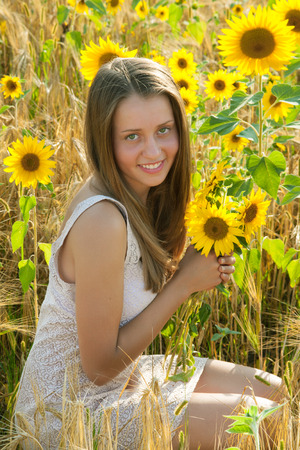 Smiling teen girl in the sunflowers field