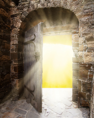 Old doors opening to show a bright light in the darkness photo
