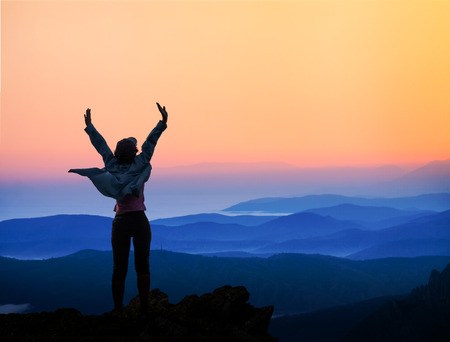 woman on top of the mountain looking to the sun